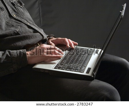 Man holding a laptop in his lap and working - stock photo