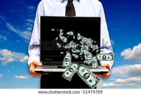 man holding a laptop with money coming out of it - stock photo