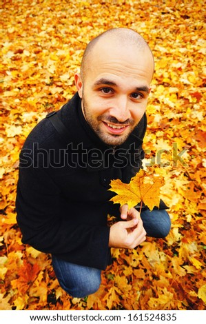 Man holding a leaf on a autumn day                                - stock photo