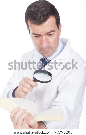 man holding a magnifying glass and pointing to a book - stock photo
