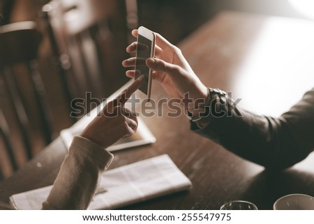 Man holding a mobile phone and woman touching its display, cafe table on background