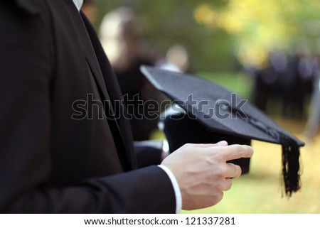 Man holding a mortar board in focus on a autumn day in Oxford - stock photo