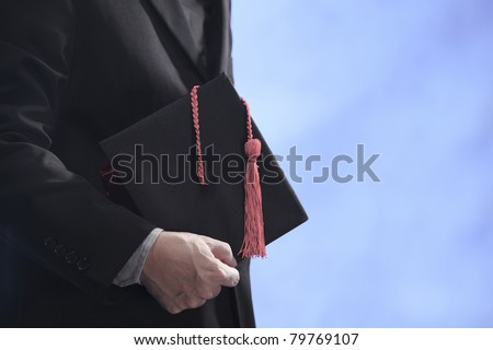 man holding a mortar board with copy space - stock photo