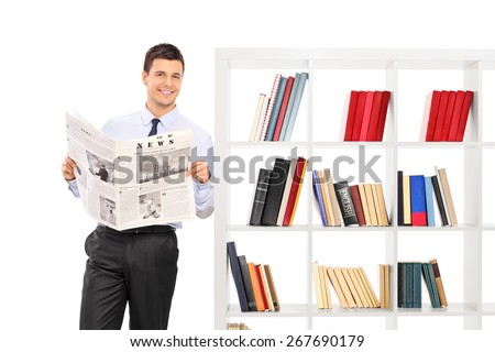 Man holding a newspaper and leaning against a bookshelf ATTENTION !!!  The newspaper is custom made, the text is Latin and the pictures are my copyright.  - stock photo