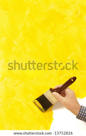 Man holding a paintbrush with a partly finished blank yellow painted wall.  Space for copy. - stock photo