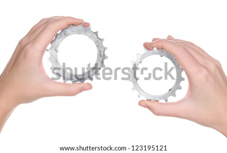 Man holding a pair of old metallic cogwheels in his hands - stock photo