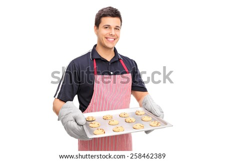 Man holding a pan full of chocolate chip cookies isolated on white background - stock photo
