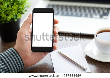 man holding a phone with isolated screen over the desk in the office - stock photo