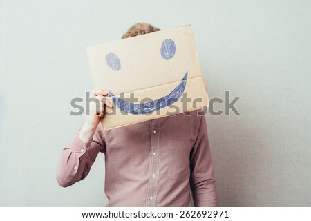 man holding a picture painted with a cheerful smiley - stock photo
