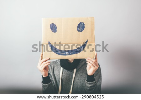 man, holding a picture with a cheerful and happy smiley - stock photo
