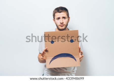man  holding a picture with a unhappy  - stock photo