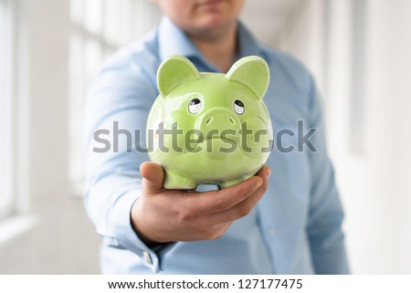 Man holding a piggy bank and throw money in it