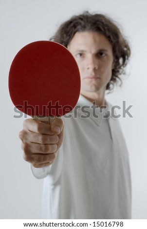Man holding a ping-pong paddle stares ahead with a serious look on his face. Vertically framed photograph. - stock photo
