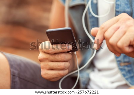 man holding a Player, listening to music - stock photo