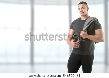 Man holding a protein shake after a workout in the gym