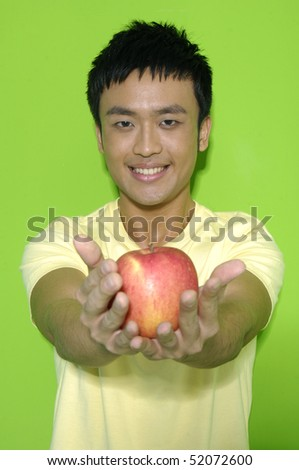 Man holding a red apple on a green background - stock photo