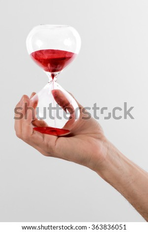 Man holding a red hourglass with hand running through te chambers measuring the passing time counting down to a deadline, over a grey background - stock photo