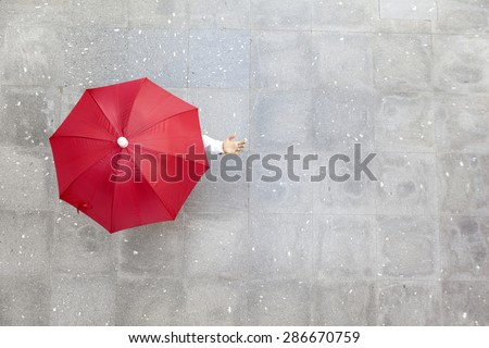 Man holding a red umbrella  - stock photo