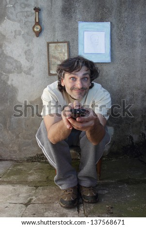 Man holding a remote control while watching TV - stock photo