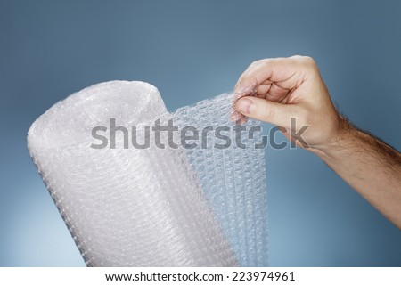 Man holding a roll of plastic bubble wrap.