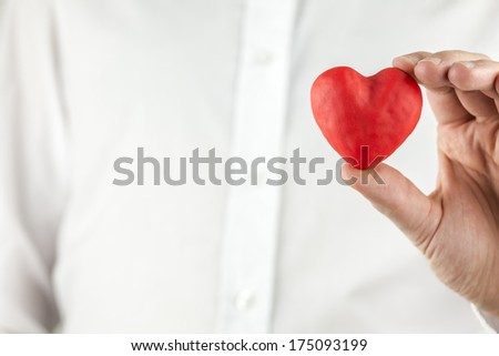 Man holding a romantic red heart symbolising love in his hand over his white shirt with copyspace for your anniversary, wedding, Valentine or engagement message to a loved one or sweetheart. - stock photo