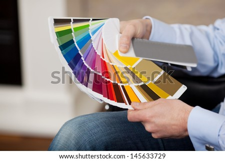 Man holding a set of paint color swatches in all the colors of the spectrum splayed out in his hand as he tries to decide on a new color for his house - stock photo