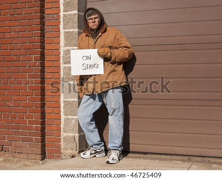 man holding a sign indicating he is on strike - stock photo