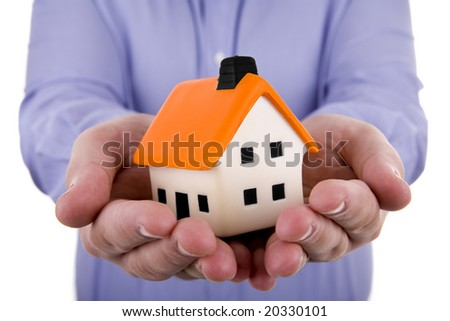 man holding a small house in his hands - stock photo