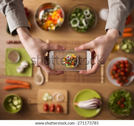 Man holding a smart phone hands close up, kitchen table worktop on background with fresh vegetables and utensils - stock photo