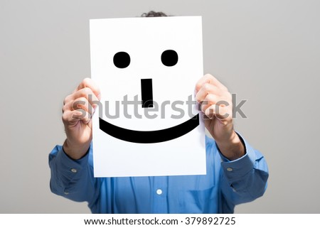 Man holding a smiling face emoticon