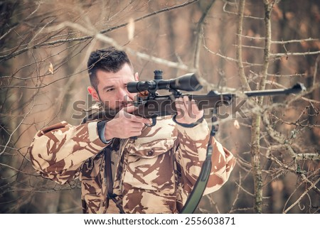 Man holding a sniper and shooting on an open season, looking through scope - stock photo
