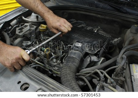 Man holding a spanner over a car engine. - stock photo