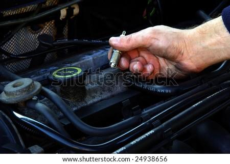 Man holding a spark plug over a car engine. - stock photo