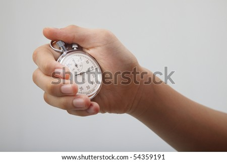 man holding a stop watch on the plain background