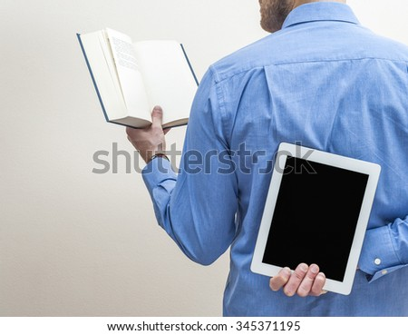 Man holding a tablet and a book