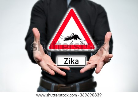 Man holding a warning sign with a mosquito and the text Zika - stock photo