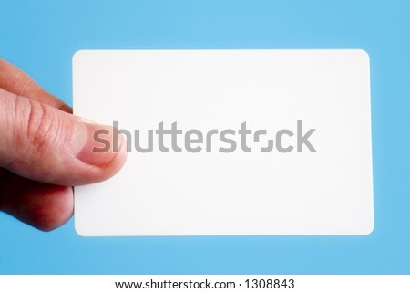Man holding a white business card on a light blue background - stock photo