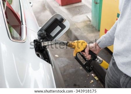 Man holding a yellow fuel pump nozzle