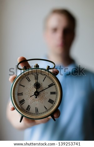 man holding an alarm clock in hands - stock photo