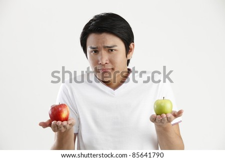 man holding an green apple and red apple