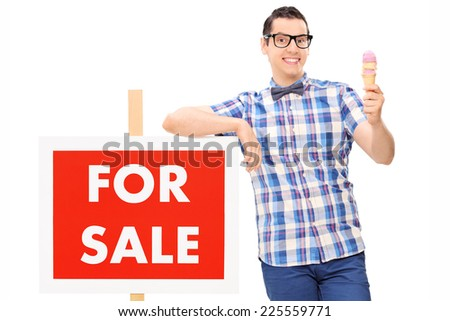 Man holding an ice cream by a for sale sign isolated on white background - stock photo