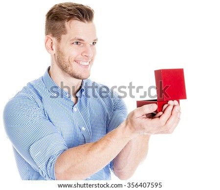 man holding an open jewelry box and looking into girlfriends eyes - stock photo