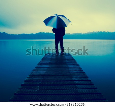 Man Holding an Umbrella on a Jetty by Tranquil Lake Concept