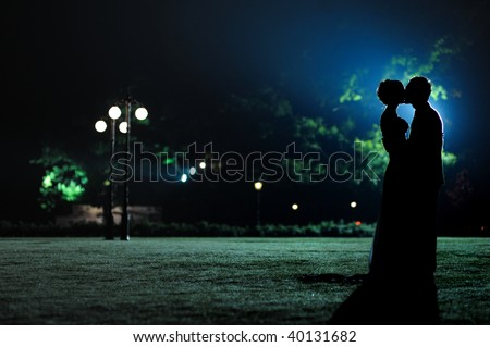 Man holding and kissing woman silhouettes in the evening park - stock photo