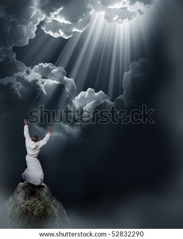 Man holding arms up in praise against sunset - stock photo