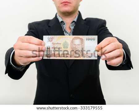 Man holding 1000 baht Thai currency banknote - stock photo