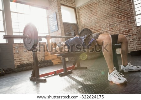 Man holding barbell lying on bench at the gym - stock photo