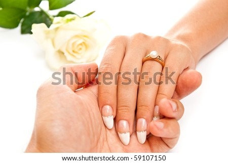 Man holding beautiful woman's hand with ring. On white background