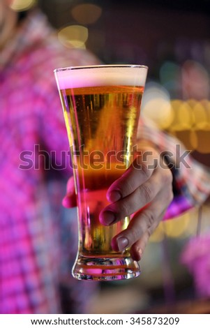 Man holding beer glass, close-up