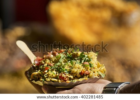 Man holding Bhelpuri plate - stock photo